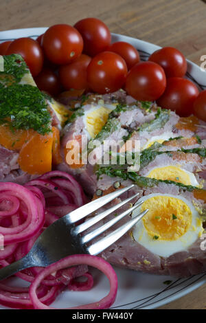 A close-up view of homemade Ham and Egg Terrine with  soused/pickled red onion and Cherry Tomatoes. - Stock Photo