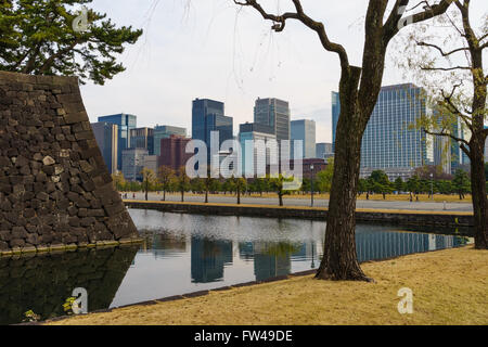 The moat and gardens at the Imperial Palace against the city skyline, Tokyo, Japan. - Stock Photo