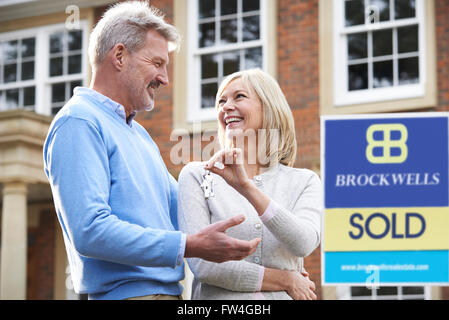 Mature Couple Happy At Getting Keys To New House - Stock Photo