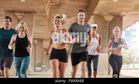Diverse adults exercising with running club group. Happy young people running together in city. - Stock Photo
