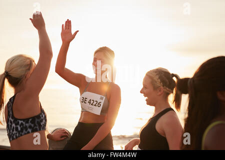 Shot of female runners high fiving each other after a race. Group of athletes giving each other high five after - Stock Photo