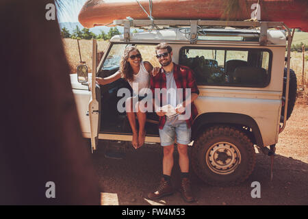 Portrait of happy young couple taking a break on roadtrip. Young man and woman enjoying on a road trip vacation. - Stock Photo