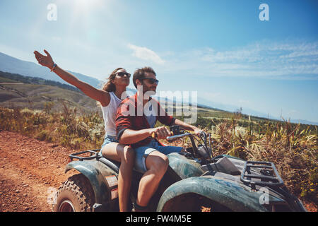 Happy young couple in nature on a quad bike. Young man and woman enjoying a quad bike ride in countryside. Man driving - Stock Photo