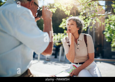 Beautiful senior woman blowing a kiss to camera while sitting outdoors on a bench in the city. Woman being photographed - Stock Photo