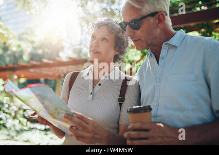 Close up portrait of senior couple using a map for directions. Retired couple exploring new places to visit during - Stock Photo