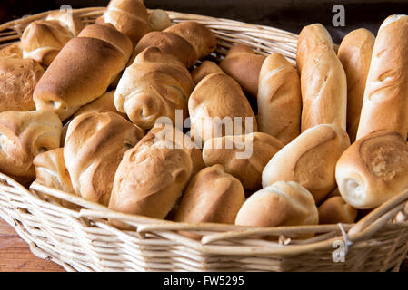 Wicker basket filled with assorted freshly baked crusty bread rolls in different shapes on display at a bakery - Stock Photo