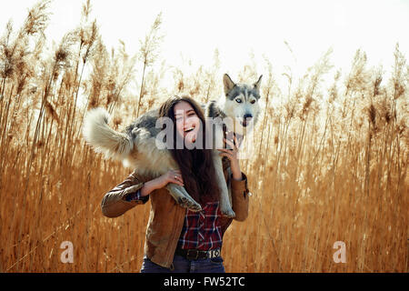 young woman playing with his Siberian husky puppy in a field during sunset. Happy smiling girl having fun with a - Stock Photo