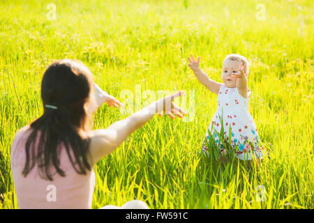 Little daughter happily running towards her mom. People having rest in sunny green meadow on spring or summer day. - Stock Photo