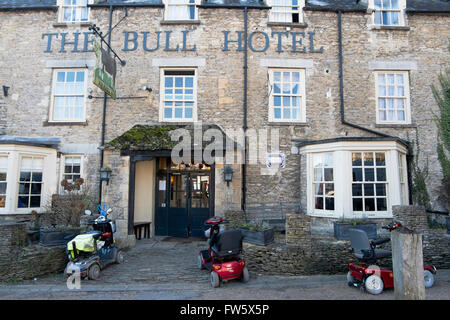 Three mobility scooters parked outside The Bull Hotel in the High Street in Fairford, Gloucestershire, UK - Stock Photo