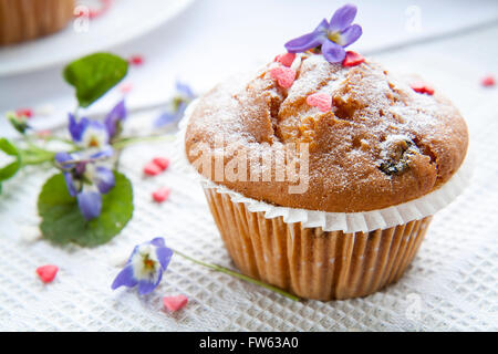Tasty muffins with sugar hearts and cup of green tea with lemon balm, blue spring flowers viola on light background - Stock Photo