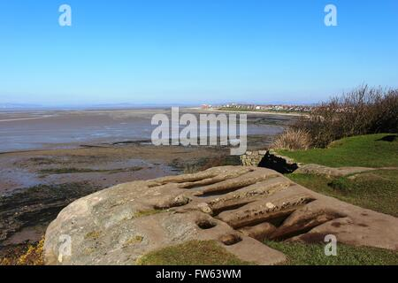 Rock cut graves by St Patrick's Chapel, Heysham, Lancashire with view along the edge of Morecambs Bay towards Morecambe - Stock Photo