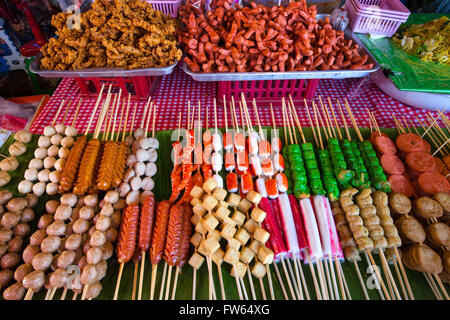 Market stall with various skewers with meat, fish and sausage, food stall, food for sale at a night market, Thailand - Stock Photo