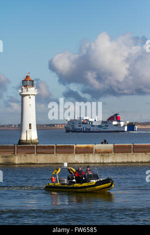 RNLI training on the boating lake, with shiping leaving the River Mersey heading for the Irish sea passing Fort - Stock Photo