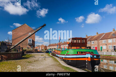 Restored barges, old winch, and town houses, along the beck (canal), with a view of the Minster on the horizon in - Stock Photo
