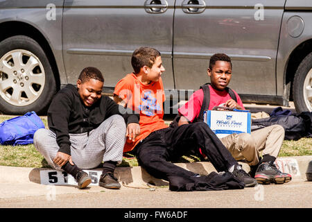 three laughing preteen boys sit on a neighborhood curb together in Oklahoma City, Oklahoma, USA. African American, - Stock Photo