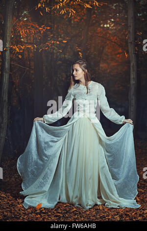 Beautiful woman posing among autumn leaves. Seasonal and fantasy - Stock Photo