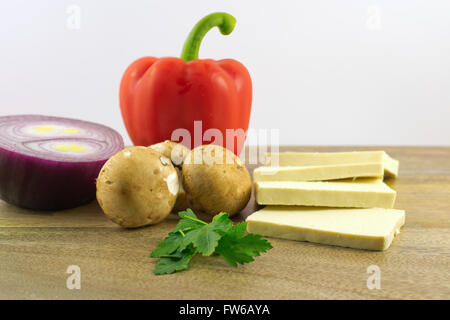 Red pepper, bit of parsley, mushrooms, red onion and sliced tofu on wooden plate against white background, selective - Stock Photo