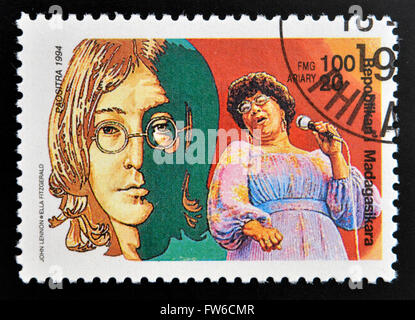 MALAGASY REPUBLIC - CIRCA 1994: A stamp printed in Madagascar shows John Lennon (1940-1980), Ella Fitzgerald (1917 - Stock Photo