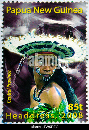 PAPUA NEW GUINEA - CIRCA 2000: Stamp printed in Papua New Guinea shows a woman in a feathered headdress - Stock Photo