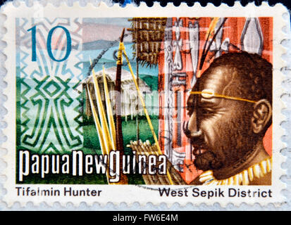 PAPUA NEW GUINEA - CIRCA 1980: A stamp printed in Papua shows Tifalmin Hunter and West Spok District, circa 1980 - Stock Photo