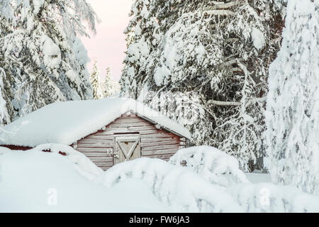 Old barn in forest among snowy trees, frosty door on the barn, plenty of snow, Gällivare, Swedish Lapland, Sweden - Stock Photo