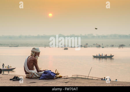 A Sadhu (Hindu religious devotee) is sitting by the holy river Ganges in Varanasi as the sun rises in the background. - Stock Photo