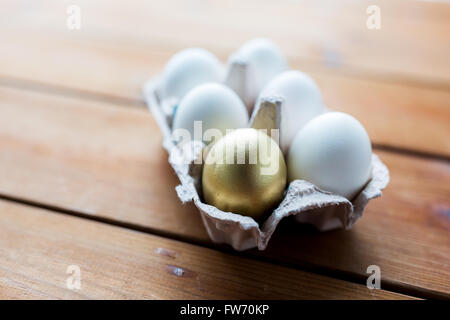 close up of white and gold eggs in egg box - Stock Photo