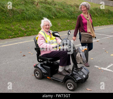Elderly woman using a mobility scooter with her carer walking beside her - Stock Photo