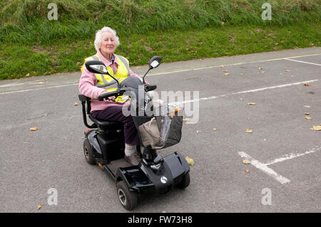 Elderly woman using a mobility scooter wearing a yellow hi-vis safety vest - Stock Photo