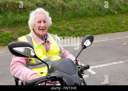 Portrait of an elderly woman sitting in her mobility scooter wearing a yellow hi-vis safety vest - Stock Photo