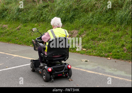 Rear view of an elderly woman using a mobility scooter wearing a yellow hi-vis safety vest - Stock Photo