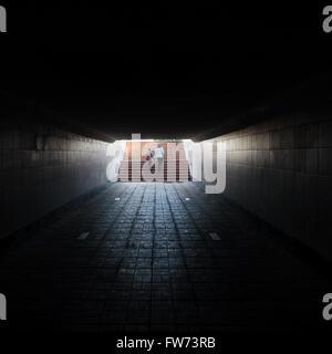 Underground, a dark crosswalk, an exit in the distance. - Stock Photo