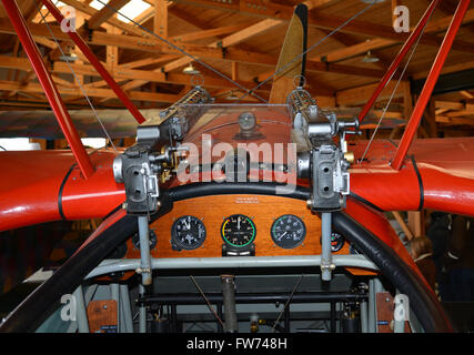 The cockpit and guns on a WWI German Fokker DR1 fighter Triplane in a hanger at the Military Aviation Museum in - Stock Photo