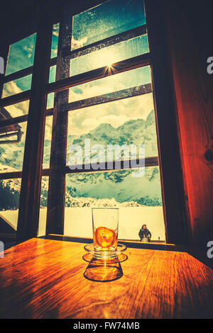 Retro stylized empty tea glass with squeezed lemon slice on wooden table with mountain view. - Stock Photo