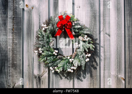 Pine wreath with red velvet bow on a vintage wooden background. - Stock Photo