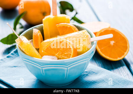 Homemade lilly pops in bowl with fruits, on wooden rustic table - Stock Photo
