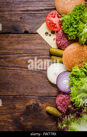 Ingredients for hamburgers on wooden table, border background with copy space for recipe or text. - Stock Photo