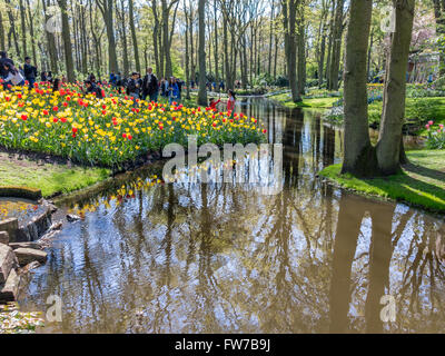 Tourists, flowers and pond in spring in Keukenhof Gardens in Lisse, South Holland, Netherlands - Stock Photo