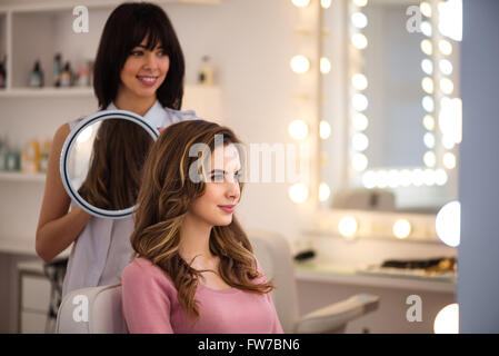 Pleasant professional hairdresser working in the salon - Stock Photo