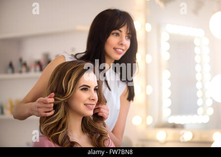 Positive professional hairdresser working on the salon - Stock Photo