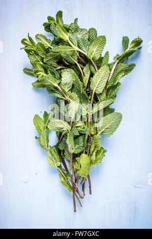 Fresh bunch of mint on wooden table, lay flat from above - Stock Photo