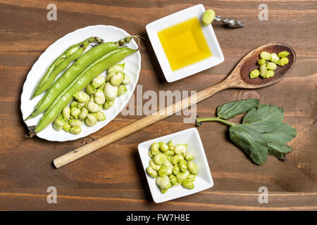 Fresh green beans seen from above on a rough wood floor brown color. Seasonings of Mediterranean cuisine: olive - Stock Photo