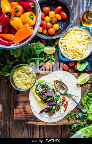 Making traditional mexican fajitas or tortillas on wooden table, street simple food. Overhead view. - Stock Photo