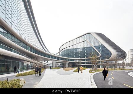 Walkway and curved glass curtain wall with pedestrians and street. Sky SOHO, Shanghai, China. Architect: Zaha Hadid - Stock Photo