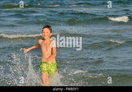 boy running through the waves at the beach - Stock Photo