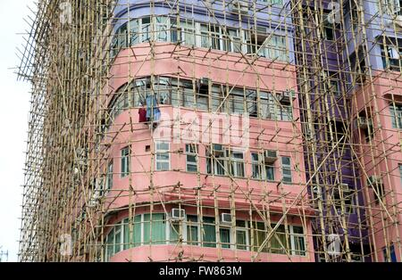 A building with bamboo scaffolding in Kowloon, Hong Kong. As bamboo is a lot cheaper than steel, but just as strong, - Stock Photo