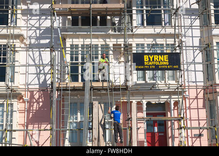 Scaffolders erecting scaffolding in UK - Stock Photo