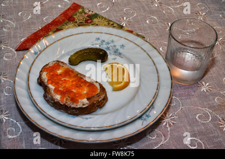 Red caviar on slice of black bread, glass of vodka, gherkin and slice of lemon. Clipping path included. - Stock Photo