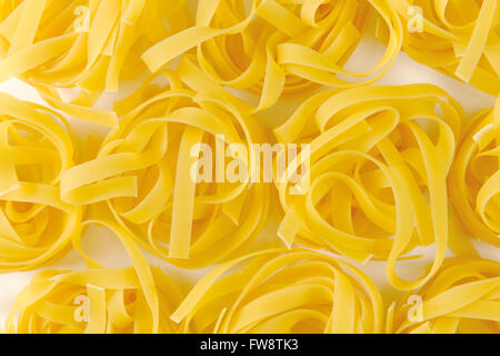 Dried ribbons of pasta coiled into nests - Stock Photo