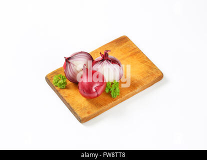whole and halved red onions on wooden cutting board - Stock Photo